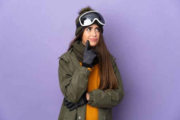 의심을 데 보라색 벽에 고립 된 스노우 보드 안경 스키 소녀