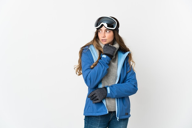 疑問と思考を持っている白い背景で隔離のスノーボードグラスを持つスキーヤーの女の子