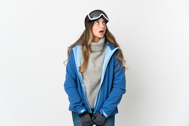 Девушка-лыжница в очках для сноуборда изолирована на белой стене, глядя вверх и с удивленным выражением лица