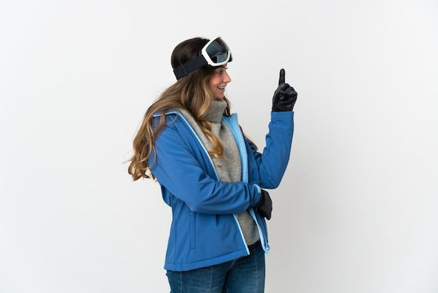 Девушка-лыжница в очках для сноуборда изолирована на белой стене, указывая на отличную идею