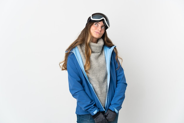 Skier girl with snowboarding glasses isolated on white background and looking up