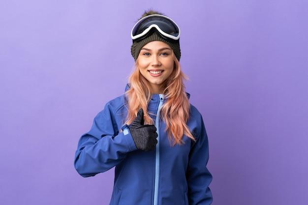 親指を立てるジェスチャーを与える孤立した紫色のスノーボードグラスを持つスキーヤーの女の子