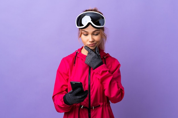 Девушка-лыжница в очках для сноуборда на изолированном фиолетовом мышлении и отправке сообщения