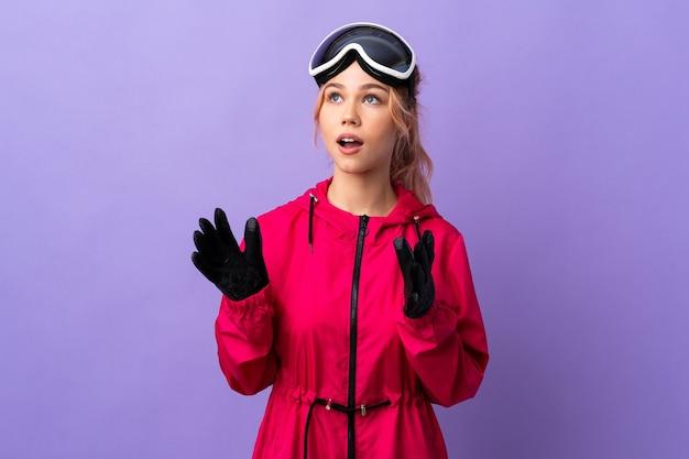 Девушка-лыжница в очках для сноуборда на изолированном фиолетовом с удивленным выражением лица