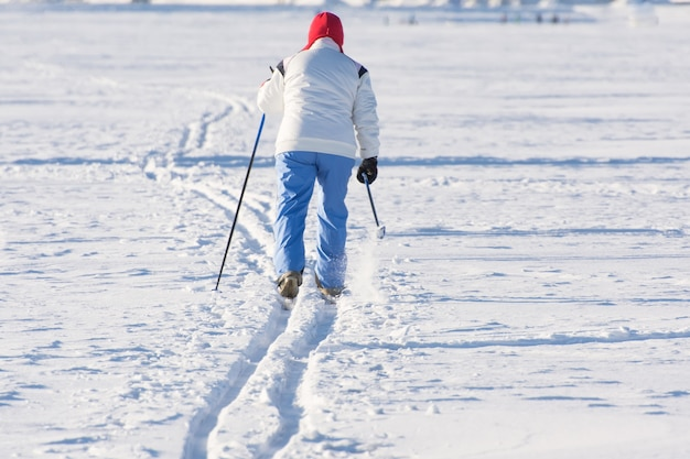 Skier goes on the track on a sunny winter day.