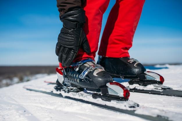 スキーヤーの手はスキーのクローズアップの固定を固定します。冬のアクティブなスポーツ、極端なライフスタイル。ダウンヒルスキー