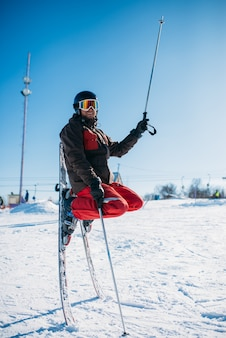 Skier in helmet and glasses posing on skis stuck with noses in the snow. winter active sport, extreme lifestyle. downhill skiing