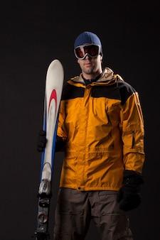 Лыжник держит пару лыж на черной стене