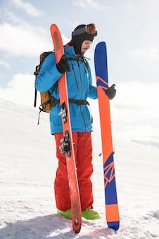 Лыжник держит лыжи в снежных горах