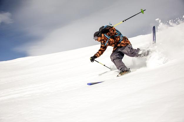 다채로운 스포츠웨어를 입은 스키어가 스키와 스키 스틱으로 산을 달려갑니다.