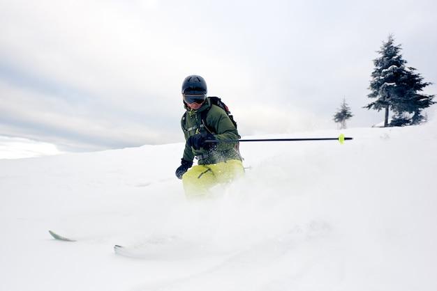 雪をかぶった下り坂で深いパウダーを着たスキーヤー。極端なスキーの概念。灰色の空と背景の松の木。正面図。