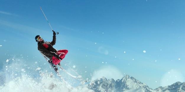 ヘルメットと眼鏡をかけたスキーヤーがジャンプし、スポーツマンがアクションを起こします。冬のアクティブスポーツ、極端なライフスタイル。山でのスキー、