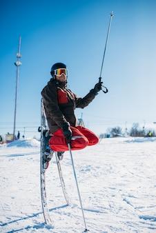 ヘルメットとスキーでポーズをとるメガネのスキーヤーが雪の中で鼻で立ち往生しています。冬のアクティブなスポーツ、極端なライフスタイル。ダウンヒルスキー