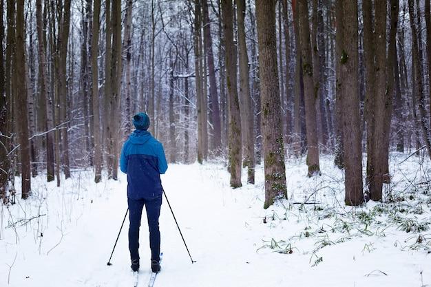 雪に覆われた森を背景に、ウインドブレーカーと帽子をかぶったスキーヤーが、背中にストックを持ったポンポンを持っています。冬の森でのクロスカントリースキー、アウトドアスポーツ、健康的なライフスタイル。