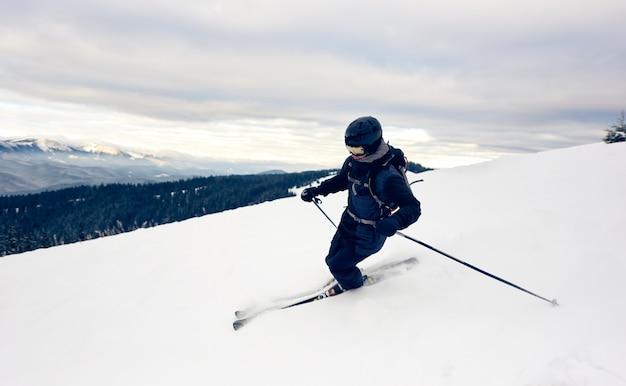雪をかぶった山頂を曲がるスキーヤー。極端なスキーの概念。山の景色。背景の灰色の空。