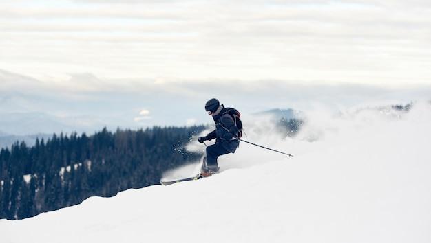 Skier inclining turning on snowcapped mountain peak
