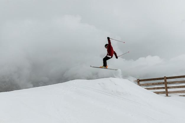Лыжник прыгает через холм, длинный выстрел