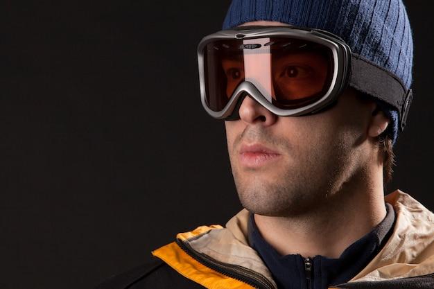 黒い壁で何かを探しているスキーヤー。