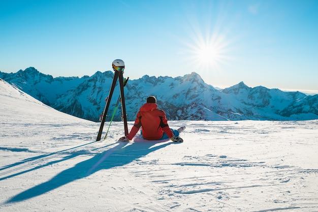 Лыжник сидит и отдыхает перед горой