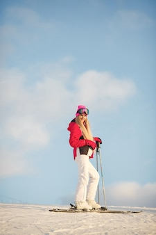 Skier on a mountain slope posing against a background of snow-capped mountains
