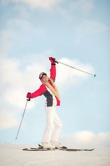 Лыжник на горном склоне позирует на фоне заснеженных гор