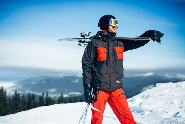 Skier poses with skis and poles in hands, blue sky and snowy mountains. winter active sport, extreme lifestyle. downhill skiing