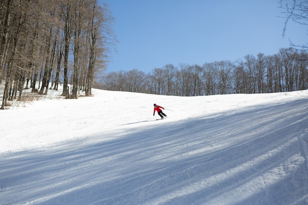 Skier in red jacket skiing downhill during sunny day in high mountains