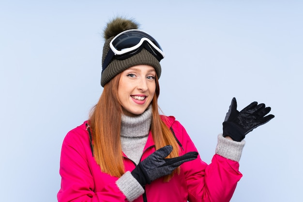 Skier redhead woman with snowboarding glasses over isolated blue wall extending hands to the side for inviting to come