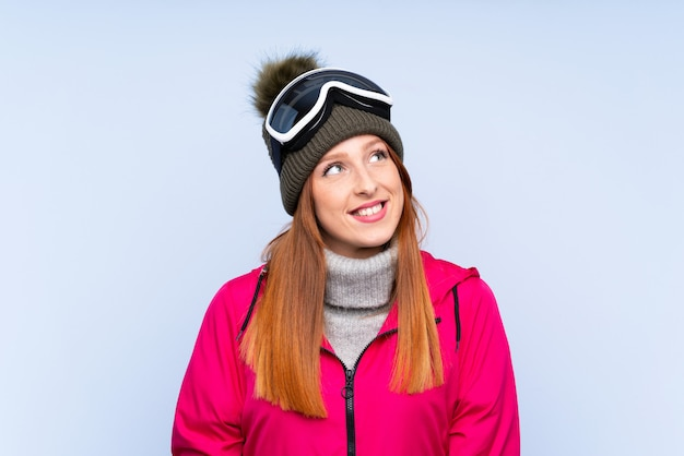 Skier redhead woman with snowboarding glasses over isolated blue wall laughing and looking up