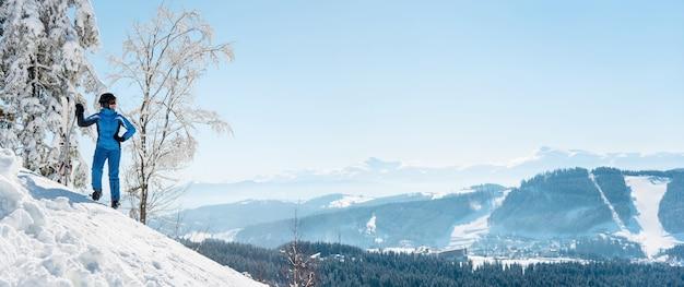 Лыжник отдыхает на вершине горы
