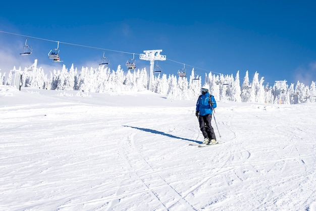 Skier riding down the hill in the mountain resort with cable cars in the background