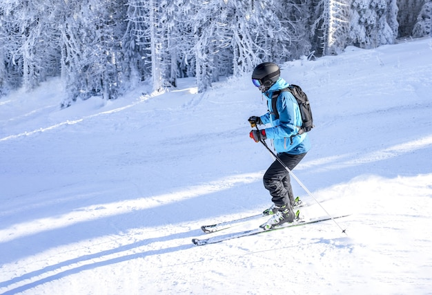 Skier riding downhill in a mountain resort