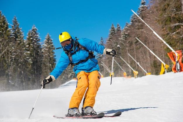 山の冬のリゾート地の斜面に乗るスキーヤー