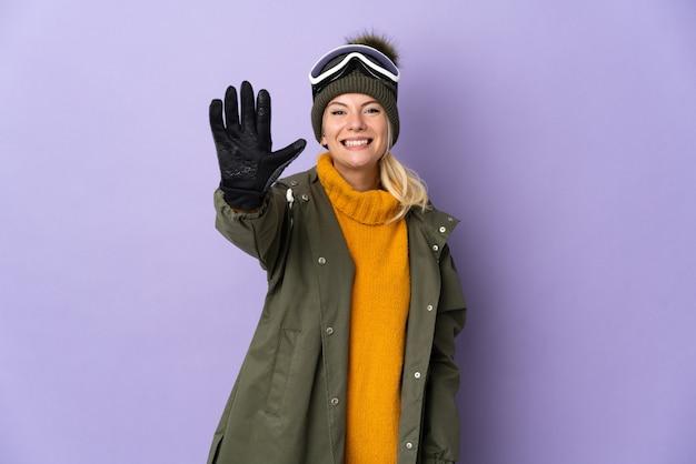 Русская девушка лыжника в очках для сноуборда изолирована на фиолетовом фоне, считая пять пальцами