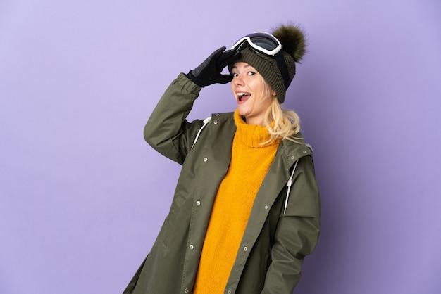 横を見ながら驚きのジェスチャーをしている紫色の背景に分離されたスノーボードグラスを持つスキーヤーロシアの女の子