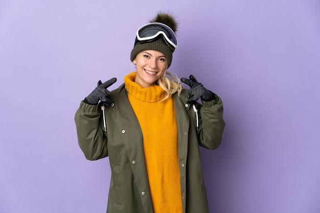 親指を立てるジェスチャーを与える紫色の背景に分離されたスノーボードグラスを持つスキーヤーロシアの女の子