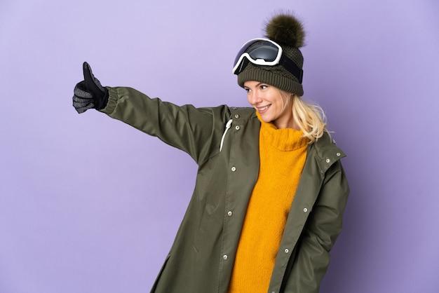 Русская девушка лыжника в очках для сноуборда изолирована на фиолетовом фоне, показывая жест рукой вверх