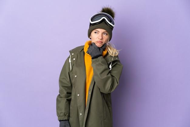 Русская девушка лыжника в очках для сноуборда изолирована на фиолетовом фоне, сомневаясь