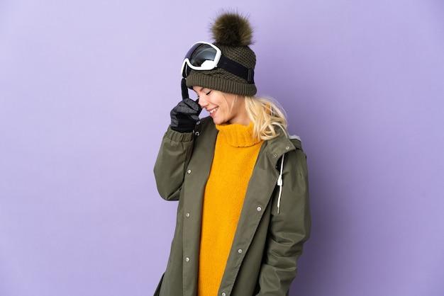 笑って紫色の背景に分離されたスノーボードグラスとスキーヤーロシアの女の子
