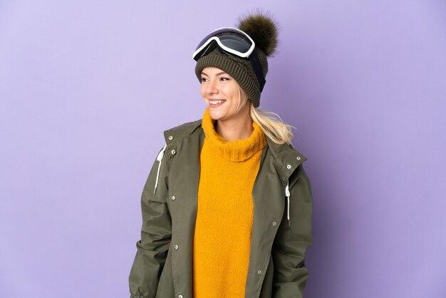 側面を見て紫色の背景に分離されたスノーボードグラスとスキーヤーロシアの女の子