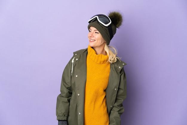 Русская девушка лыжника в очках для сноуборда изолирована на фиолетовом фоне, смотрит в сторону и улыбается