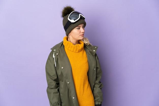 Русская девушка лыжника в очках для сноуборда изолирована на фиолетовом фоне, глядя в сторону