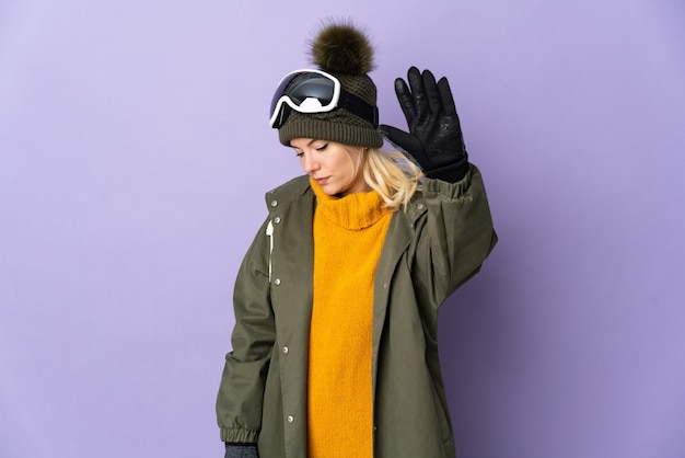 Русская девушка лыжника в очках для сноуборда изолирована на фиолетовом фоне, делая жест стоп и разочарована