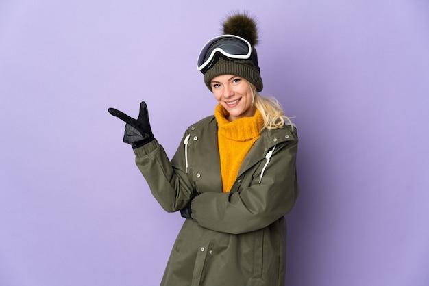 横に指を指している紫色の背景に分離されたスノーボードグラスを持つスキーヤーロシアの女の子