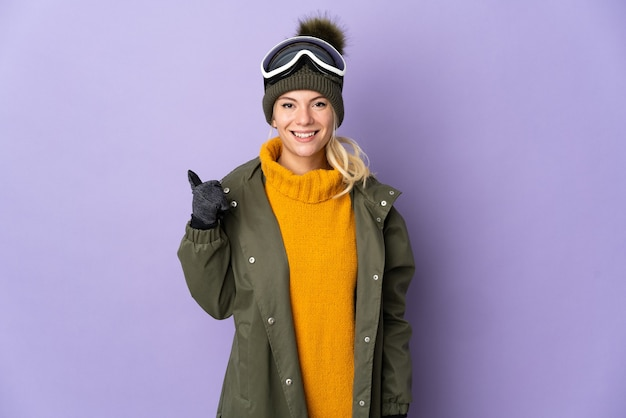 Русская девушка лыжника в очках для сноуборда изолирована на фиолетовом фоне, указывая в сторону, чтобы представить продукт