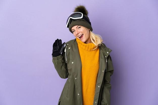 Русская девушка лыжника в очках для сноубординга изолирована на фиолетовом фоне, салютуя рукой с счастливым выражением лица