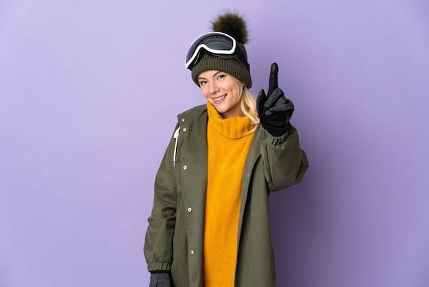 Русская девушка лыжника в очках для сноуборда, изолированные на фиолетовом фоне, показывает и поднимает палец