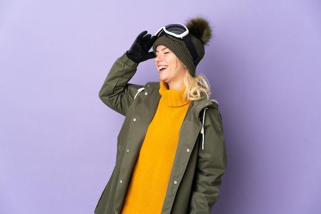 Русская девушка лыжника в очках для сноуборда изолирована на фиолетовом фоне, много улыбаясь