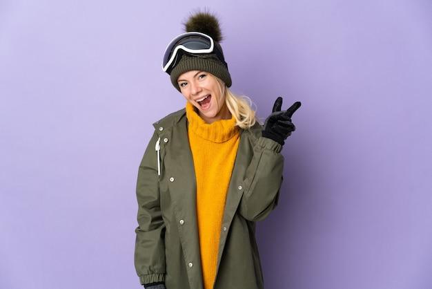 笑顔と勝利のサインを示す紫色の背景に分離されたスノーボードグラスを持つスキーヤーロシアの女の子