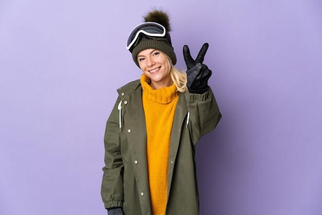 Русская девушка лыжника в очках для сноуборда, изолированные на фиолетовом фоне, улыбается и показывает знак победы